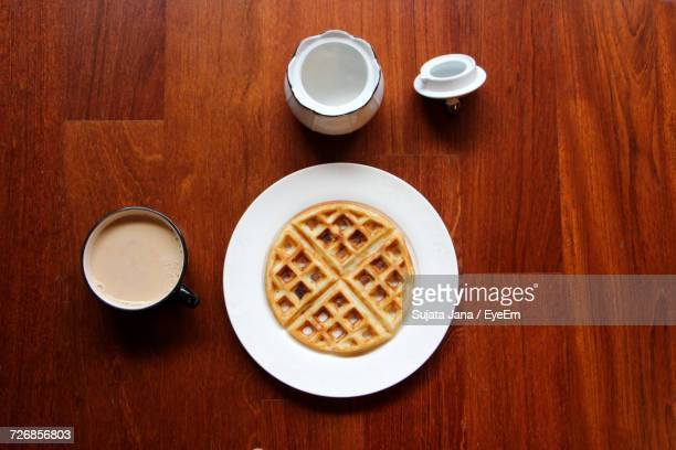 directly above shot of waffle and tea on wooden table - waffle stock photos and pictures
