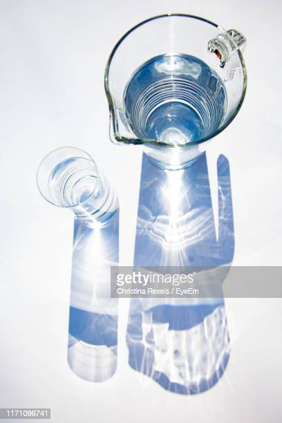 directly above shot of water jug and glass on gray background - reflet photos et images de collection