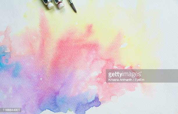 directly above shot of watercolor paint splash on gray background - pink tube photos et images de collection