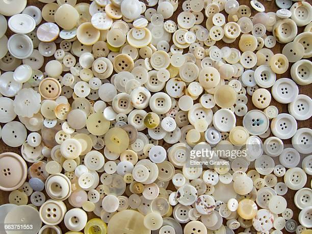 directly above shot of white buttons on table - botón mercería fotografías e imágenes de stock
