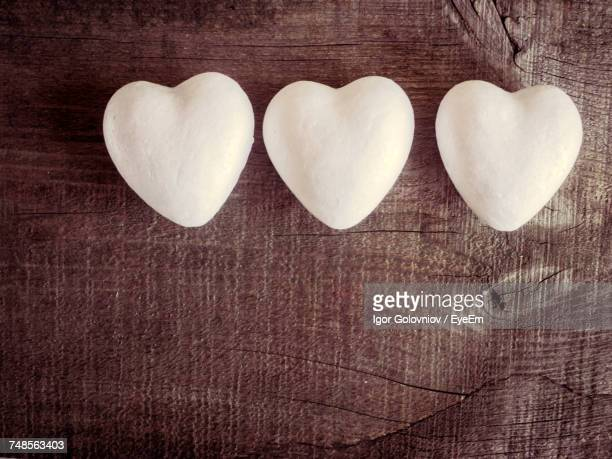 directly above shot of white heart shapes on wooden table - igor golovniov stock pictures, royalty-free photos & images
