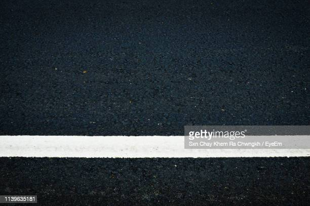 directly above shot of white line on road - 境界線 ストックフォトと画像