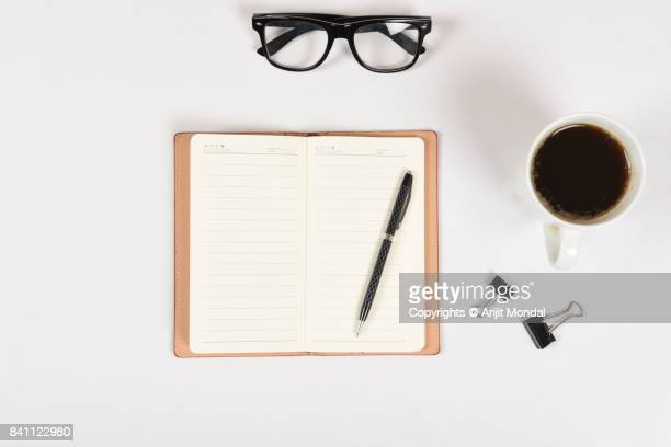 Directly above shot of white office table with notebook page, pen, spectacle, coffee cup
