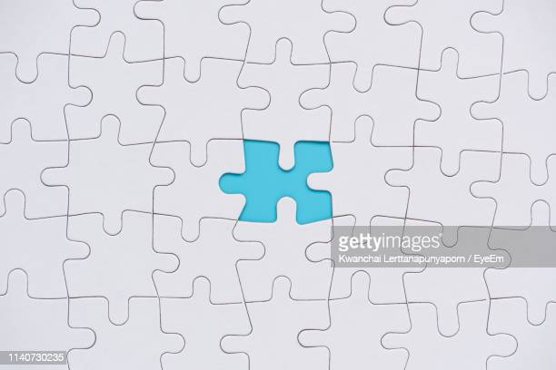 directly above shot of white puzzle on blue background - パズル ストックフォトと画像