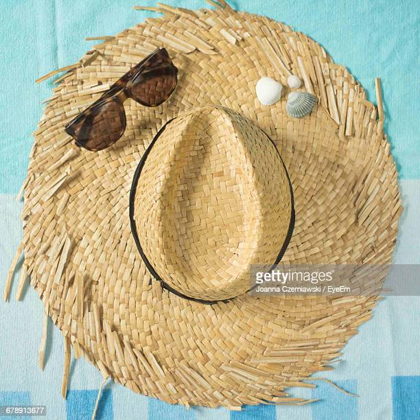 directly above shot of wicker hat with sunglasses and seashells on table - beige hat stock photos and pictures
