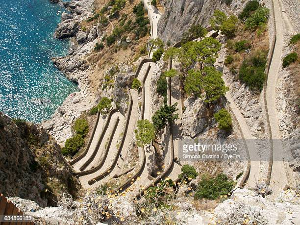 Directly Above Shot Of Winding Road On Rock Formations By Sea
