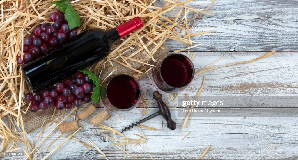 Directly Above Shot Of Wine With Bottle And Grapes On Straws At Table : Stock Photo