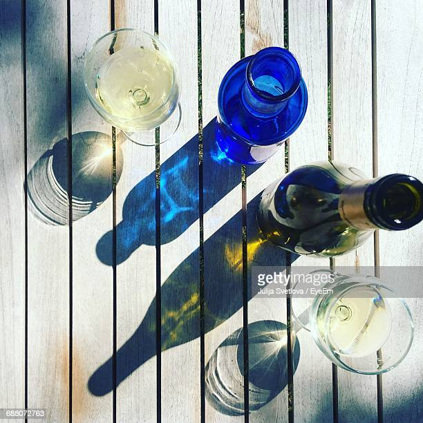 Directly Above Shot Of Wineglass And Bottles On Table During Sunny Day