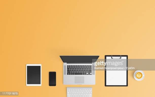 directly above shot of wireless technology by clipboard and coffee cup against yellow background - flat lay stock pictures, royalty-free photos & images