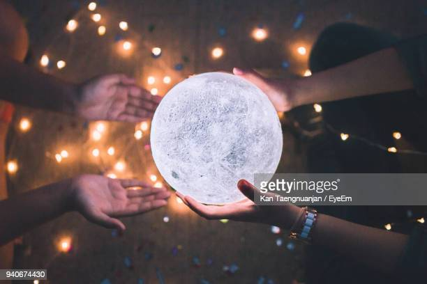 Directly Above Shot Of Woman Giving Illuminated Crystal Ball To Friend