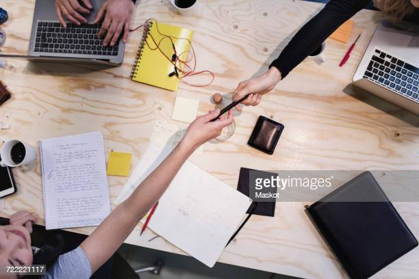 Directly above shot of woman giving pen to colleague at wooden desk