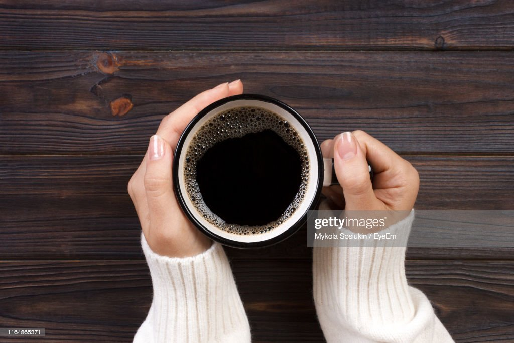 Directly Above Shot Of Woman Hands Holding Black Coffee In Cup On Table : Stockfoto
