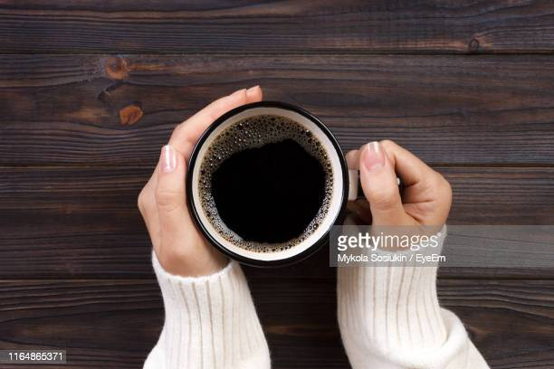 directly above shot of woman hands holding black coffee in cup on table - chávena imagens e fotografias de stock