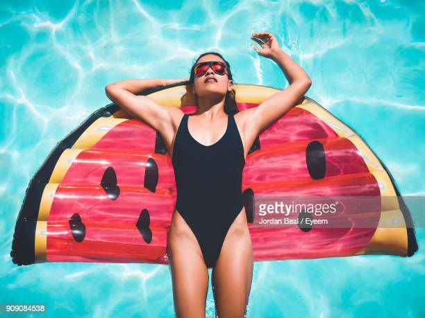 directly above shot of woman in swimwear relaxing on swimming pool - swimwear stock photos and pictures