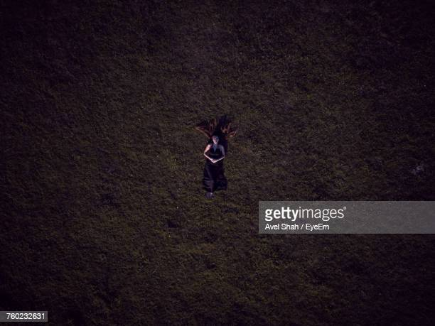 Directly Above Shot Of Woman Lying On Field