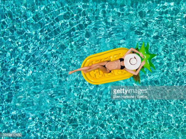 Directly Above Shot Of Woman Lying Pool Raft While Floating On Swimming Pool