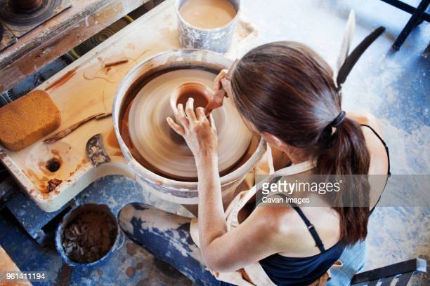 Directly above shot of woman making clay pots at workshop
