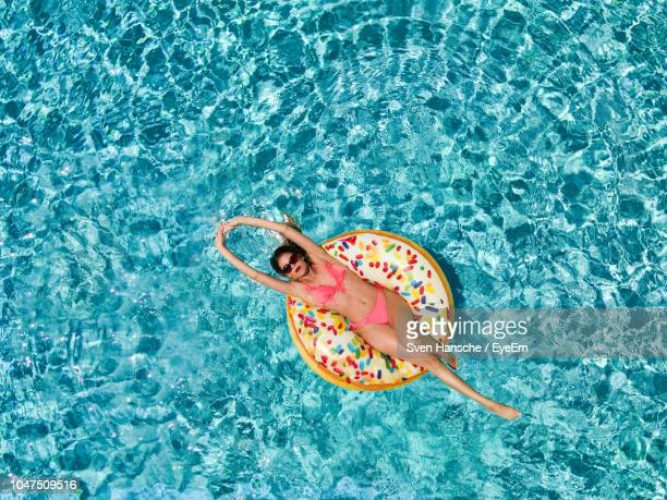 directly above shot of woman on pool raft floating in swimming pool - inflatable raft stock pictures, royalty-free photos & images