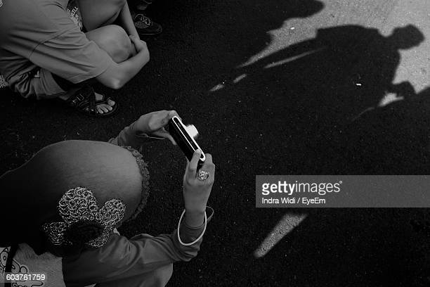 Directly Above Shot Of Woman Photographing On Street