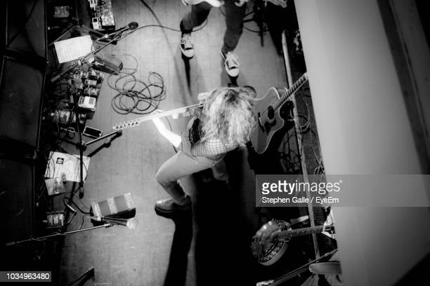 directly above shot of woman playing guitar on stage - guitariste photos et images de collection