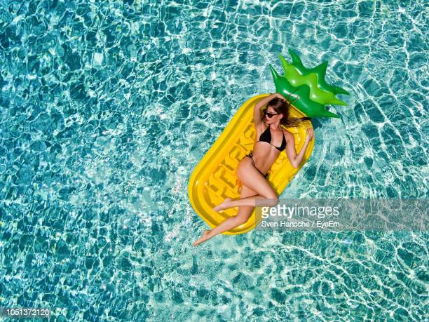 directly above shot of woman relaxing on pool raft - bikini stock pictures, royalty-free photos & images