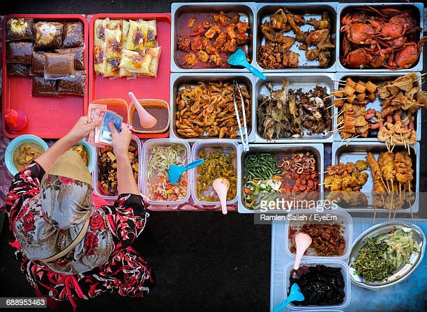 directly above shot of woman standing at food stall - malaysia stock pictures, royalty-free photos & images
