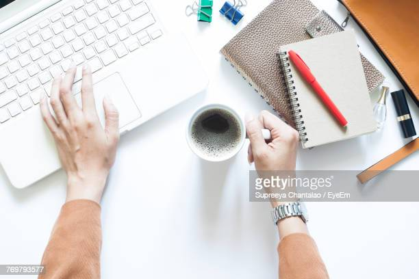 Directly Above Shot Of Woman With Black Coffee Using Laptop At Desk