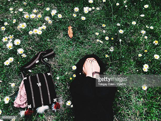 Directly Above Shot Of Woman With Covered Face Lying On Grassy Field