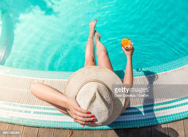 directly above shot of woman with drink sitting at poolside - sun hat stock pictures, royalty-free photos & images