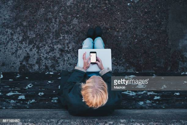 Directly above shot of woman with laptop using mobile phone while sitting on bench against retaining wall