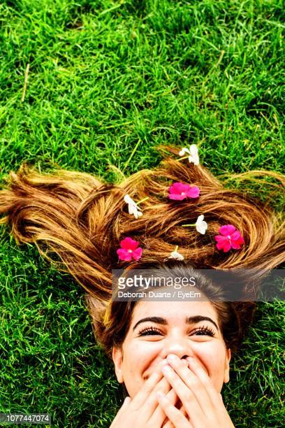 Directly Above Shot Of Woman With Long Hair Lying Down On Field
