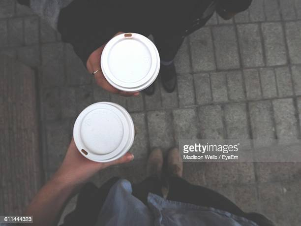 Directly Above Shot Of Women Holding Disposable Coffee Cups