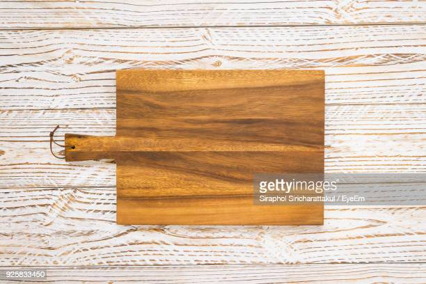 directly above shot of wooden cutting board on table - cutting board stock pictures, royalty-free photos & images