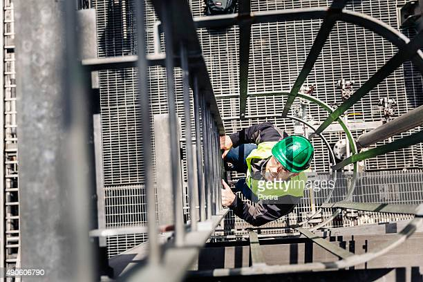 Directly above shot of worker climbing ladder in factory