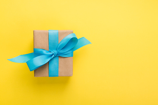 Directly Above Shot Of Wrapped Gift Box Over Yellow Background - gettyimageskorea