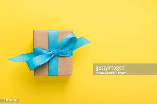 directly above shot of wrapped gift box over yellow background - caja de regalo fotografías e imágenes de stock