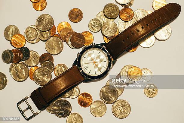 Directly Above Shot Of Wrist Watch And Coins On Table
