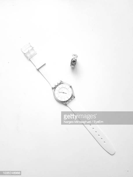 directly above shot of wristwatch with ring on white background - wrist watch stock pictures, royalty-free photos & images