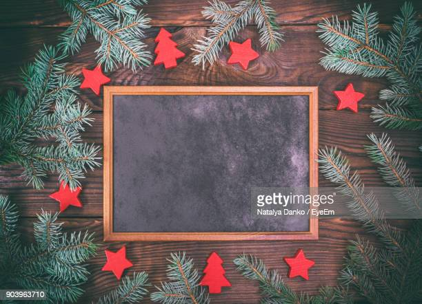 Directly Above Shot Of Writing Slate Amidst Pine Needles On Table