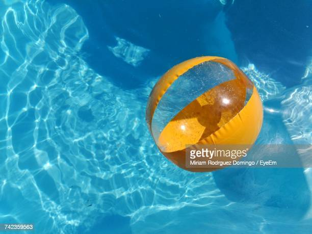 Directly Above Shot Of Yellow Inflatable Ball In Swimming Pool