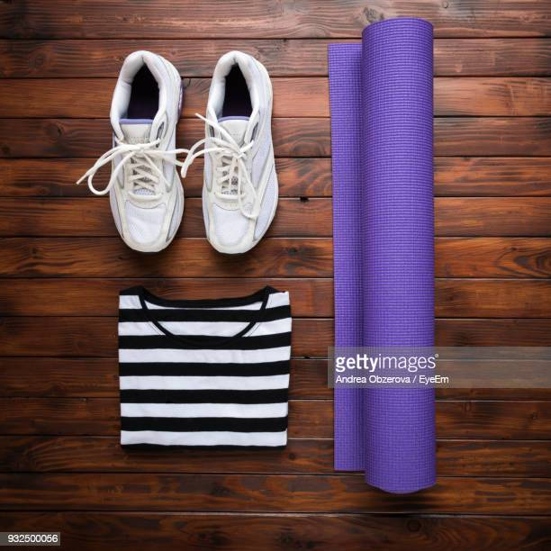 directly above shot of yoga accessories on hardwood floor - purple shoe stock pictures, royalty-free photos & images
