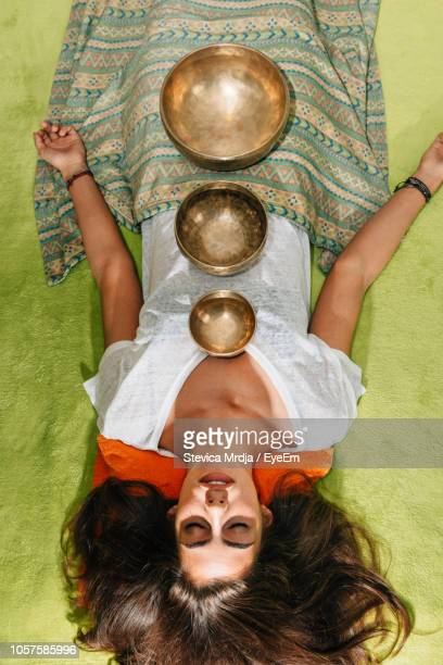 directly above shot of young woman with rin gongs sleeping at spa - rin gong stock pictures, royalty-free photos & images