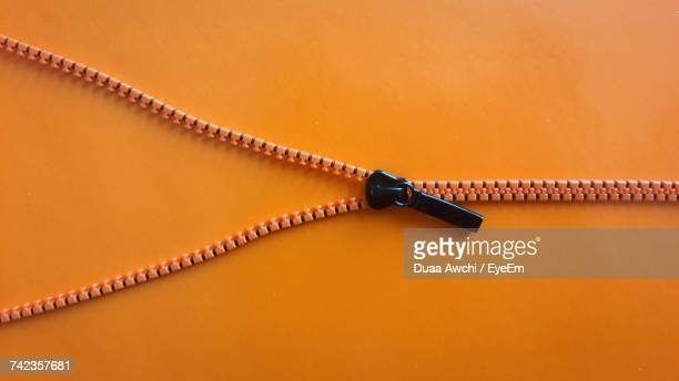 Directly Above Shot Of Zipper On Orange Background
