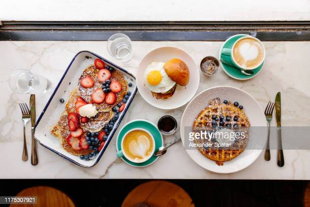 directly above view of a brunch with pancakes, waffle and burger with fried egg in a restaurant - the brunch stock pictures, royalty-free photos & images
