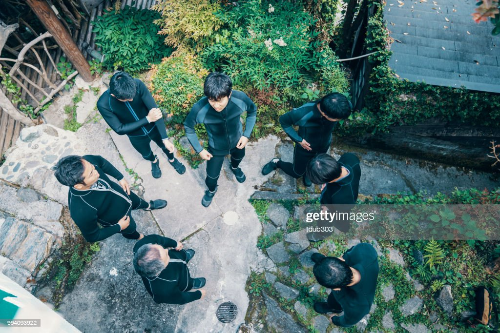 Directly above view of a group of men wearing wet suits before a river rafting tour : Foto stock