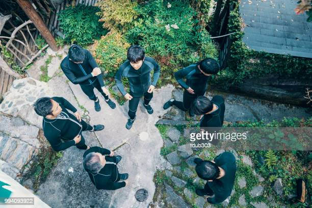 Directly above view of a group of men wearing wet suits before a river rafting tour