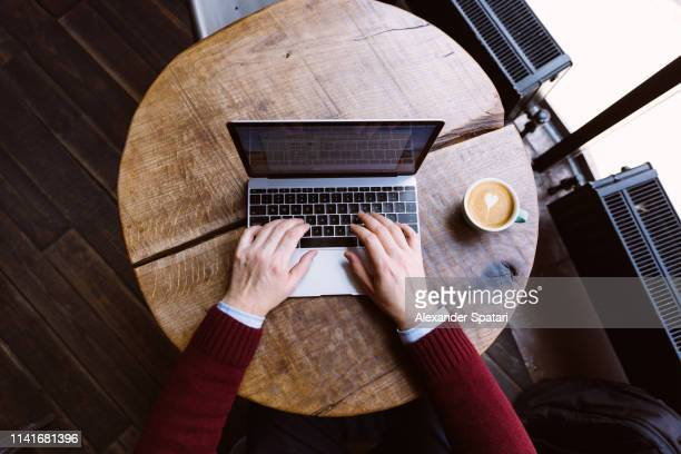 directly above view of a man working on laptop in coffee shop, personal perspective view - parte do corpo humano imagens e fotografias de stock