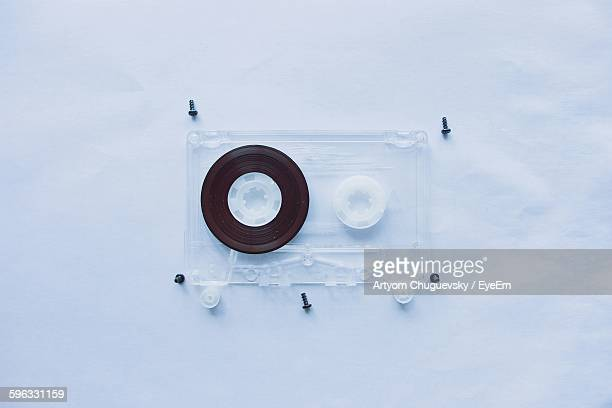 Directly Above View Of Audio Cassette With Screws On White Background