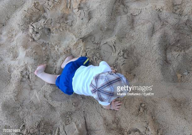 directly above view of baby boy crawling on sand at beach - marek stefunko stock pictures, royalty-free photos & images