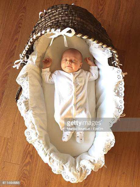 Directly Above View Of Baby Sleeping In Wicker Baby Carriage On Hardwood Floor